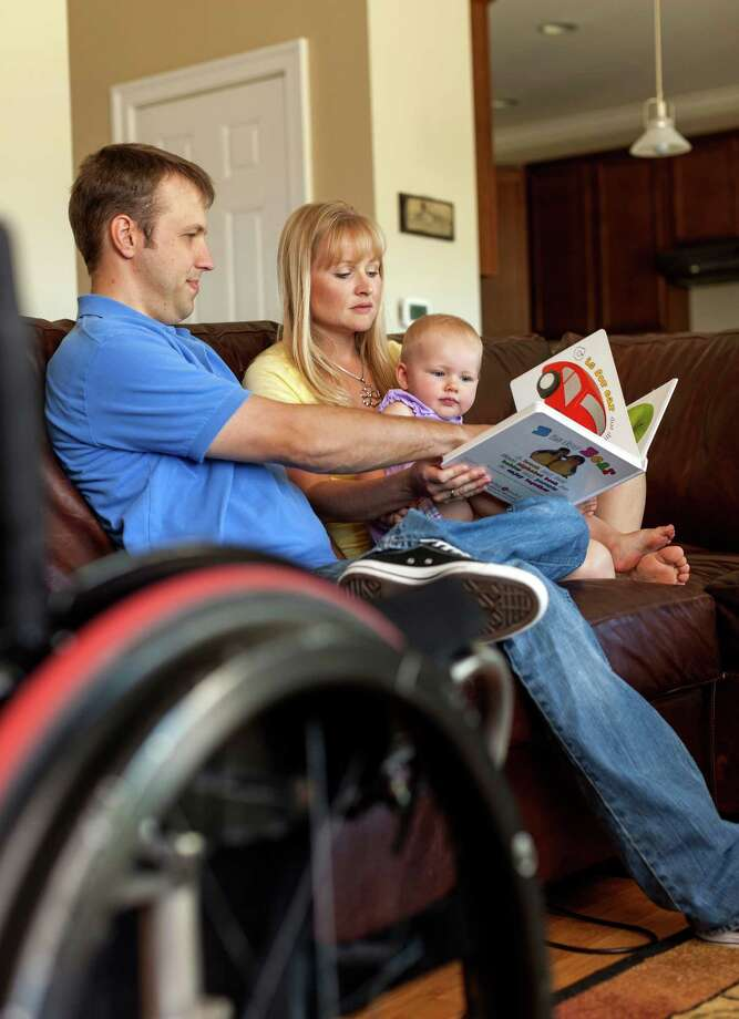 In this photo taken Aug. 6, 2012, Chuck and Brenda Isaacson read to their 16-month old daughter at their home in Sun Prairie, Wis. A bill being considered in the Senate would expand the VA's medical benefits package so other veterans, and their spouses or surrogates, don't have to bear the same expense. The department currently covers a range of medical treatment for veterans, including some infertility care, but the legislation would authorize the VA to cover the cost of IVF and to pay for procedures now covered for some critically injured active-duty soldiers. (AP Photo/Andy Manis) Photo: Andy Manis, Associated Press / FR19153 AP