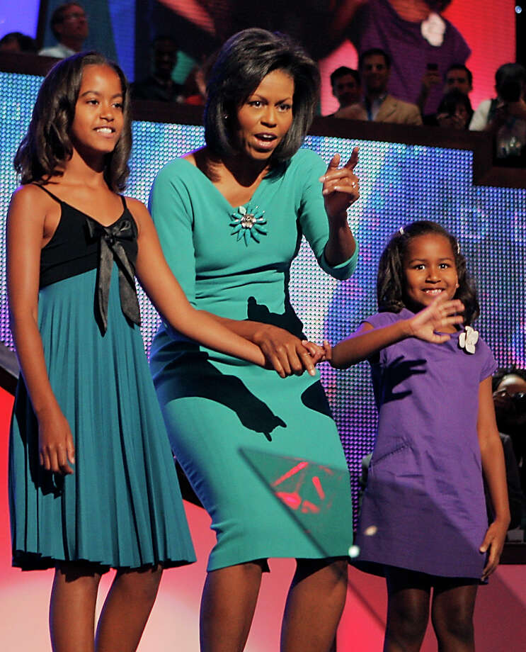 FILE -  In this Aug. 25, 2008, file photo, Michelle Obama, wife of then-Democratic presidential candidate, Sen. Barack Obama, D-Ill., and daughters Malia, left, 10, and Sasha, right,  7, wave to the audience the Democratic National Convention in Denver. Michelle is 5-foot-11, and she is world-famous. Sometimes she inspires awe in her admirers. She has been accused of being the angry type. So when Michelle Obama meets people, she likes to bring things down to earth with a hug.  (AP Photo/Jae C. Hong, File) Photo: Jae C. Hong