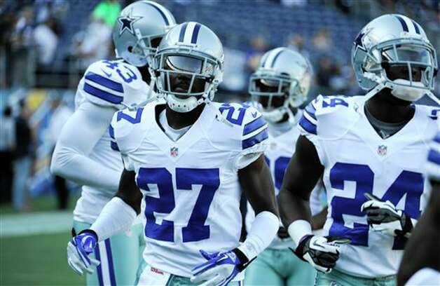Dallas Cowboys defensive back C.J. Wilson, left,  leads his teammates through drills during warmups prior to the start of a NFL preseason football game Saturday, Aug. 18, 2012 in San Diego. (AP Photo/Denis Poroy) Photo: Associated Press