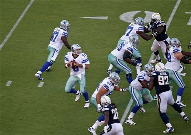 Dallas Cowboys quarterback Tony Romo stands behind the protective wall of his offensive line as they block the rush of the San Diego Chargers during the first quarter of a NFL preseason football game Saturday, Aug. 18, 2012 in San Diego. (AP Photo/Lenny Ignelzi) Photo: Associated Press