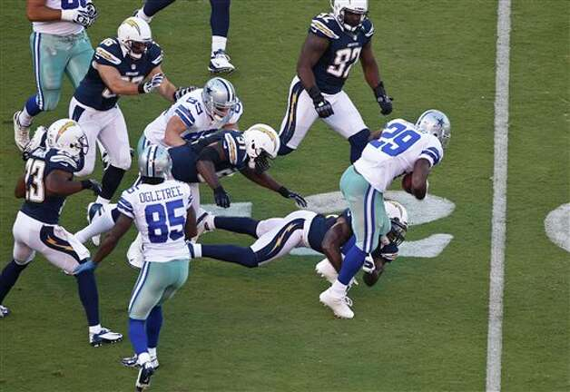 Dallas Cowboys running back DeMarco Murray breaks through the defense of the San Diego Chargers after catching a short pass during the first quarter  of a NFL preseason football game Saturday, Aug. 18, 2012 in San Diego. The tackle is made by linebacker Donald Butler.  (AP Photo/Lenny Ignelzi) Photo: Associated Press