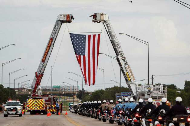 Police Officers drive under a large flag during the Law Enforcement and Emergency Services Processional after the funeral service for Brazos County Precinct 1 Constable Brian Bachmann at Reed Arena on the Texas A&M University Campus, Saturday in College Station.  Bachmann was fatally shot while serving an eviction notice to 35-year-old gunman Tres Caffall. Photo: Michael Paulsen, Houston Chronicle / © 2012 Houston Chronicle