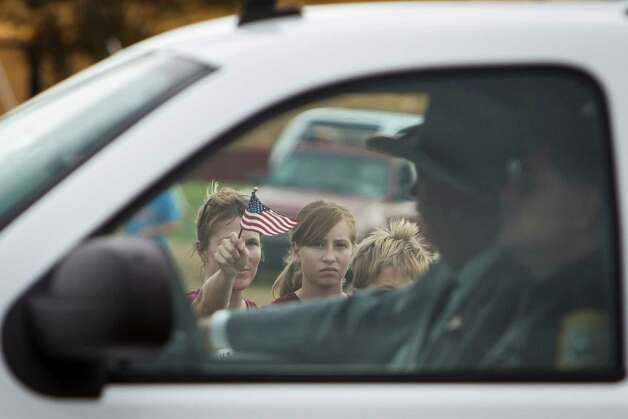 Jennifer Halling, center, points a flag as people gather for the Law Enforcement and Emergency Services Processional after the funeral service for Brazos County Precinct 1 Constable Brian Bachmann at Reed Arena on the Texas A&M University Campus, Saturday in College Station.  Bachmann was fatally shot while serving an eviction notice to 35-year-old gunman Tres Caffall. Photo: Michael Paulsen, Houston Chronicle / © 2012 Houston Chronicle
