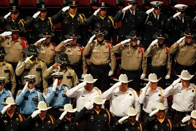 Law enforcement personnel salute Brazos County Precinct 1 Constable Brian Bachmann during the funeral service at Reed Arena on the Texas A&M University Campus, Saturday in College Station.  Bachmann was fatally shot while serving an eviction notice to 35-year-old gunman Tres Caffall. Photo: Michael Paulsen, Houston Chronicle / © 2012 Houston Chronicle