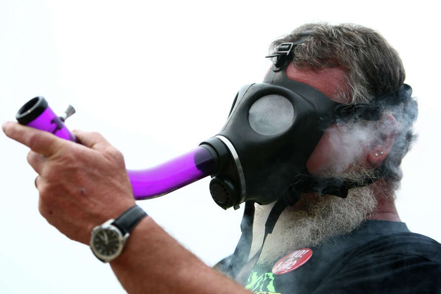 Brian from Snohomish inhales marijuana smoke from a gas mask.