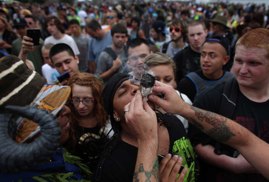 Participants smoke a large joint. Photo: JOSHUA TRUJILLO / SEATTLEPI.COM