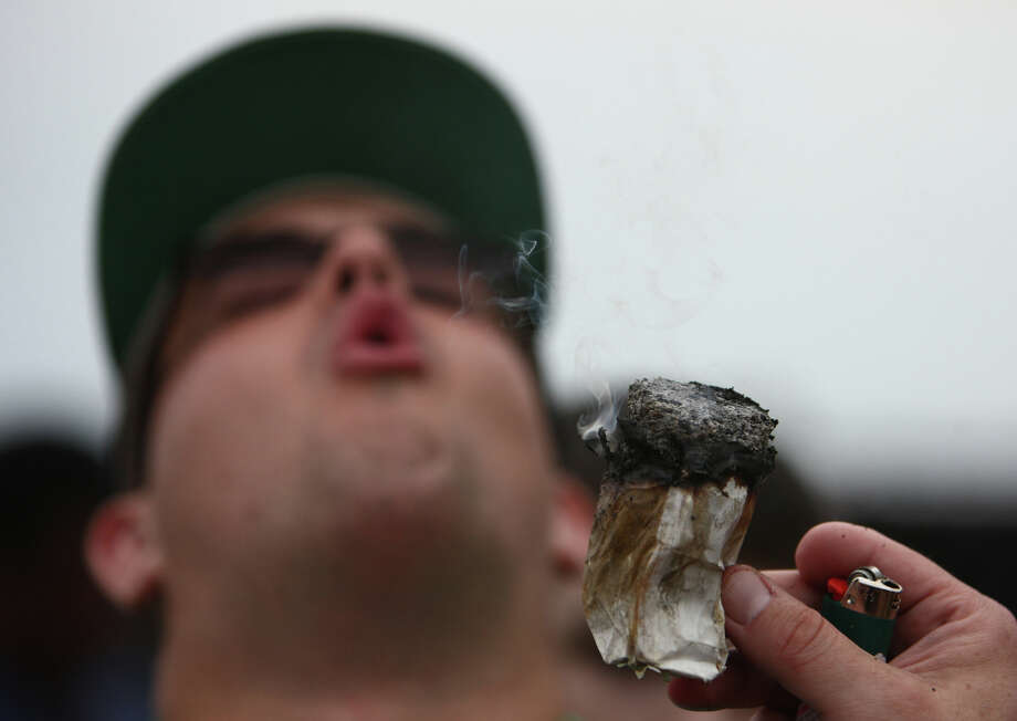 A participant inhales smoke from a large joint. Photo: JOSHUA TRUJILLO / SEATTLEPI.COM