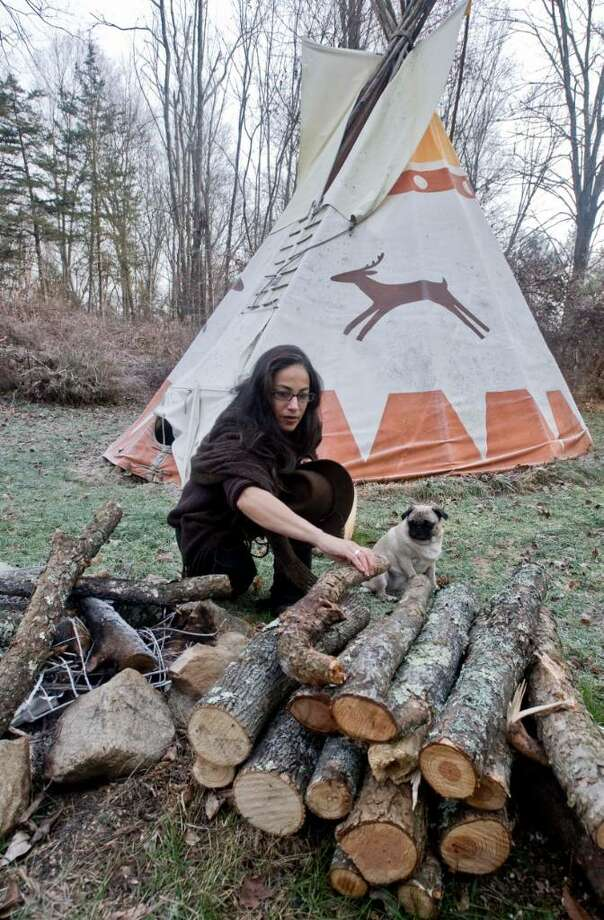 "Judy Apicella organizes the firewood at the teepees which are used for storytelling and other events on the alpaca farm in New Milford. The farm is also a bed and breakfast and has ""Farm Days"" for folks to come and visit. Wednesday, Dec. 2, 2009 Photo: Scott Mullin / The News-Times"