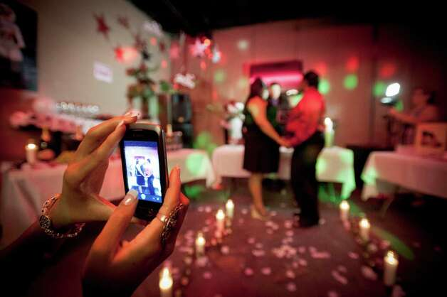 A spectator snaps a mobile phone photo during a covenant of love ceremony, Saturday, Aug. 18, 2012, at Wax Club Lounge in San Antonio. Photo: Darren Abate, Darren Abate/For The Express-New