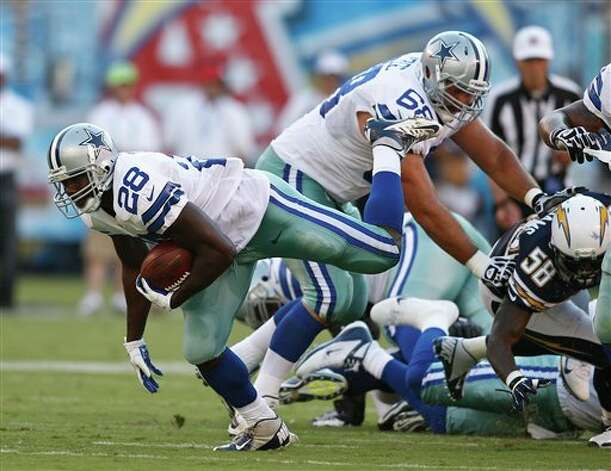 Dallas Cowboys running back Felix Jones tries to keep his balance as he slides through the San Diego Chargers defense during the first half  of a NFL preseason football game Saturday, Aug. 18, 2012 in San Diego. (AP Photo/Chris Park) Photo: Associated Press