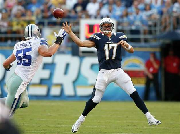 San Diego Chargers quarterback Philip Rivers gets off a pass against the rush of Dallas Cowboys linebacker Alex Albright during the first half  of a NFL preseason football game Saturday, Aug. 18, 2012 in San Diego. (AP Photo/Chris Park) Photo: Associated Press