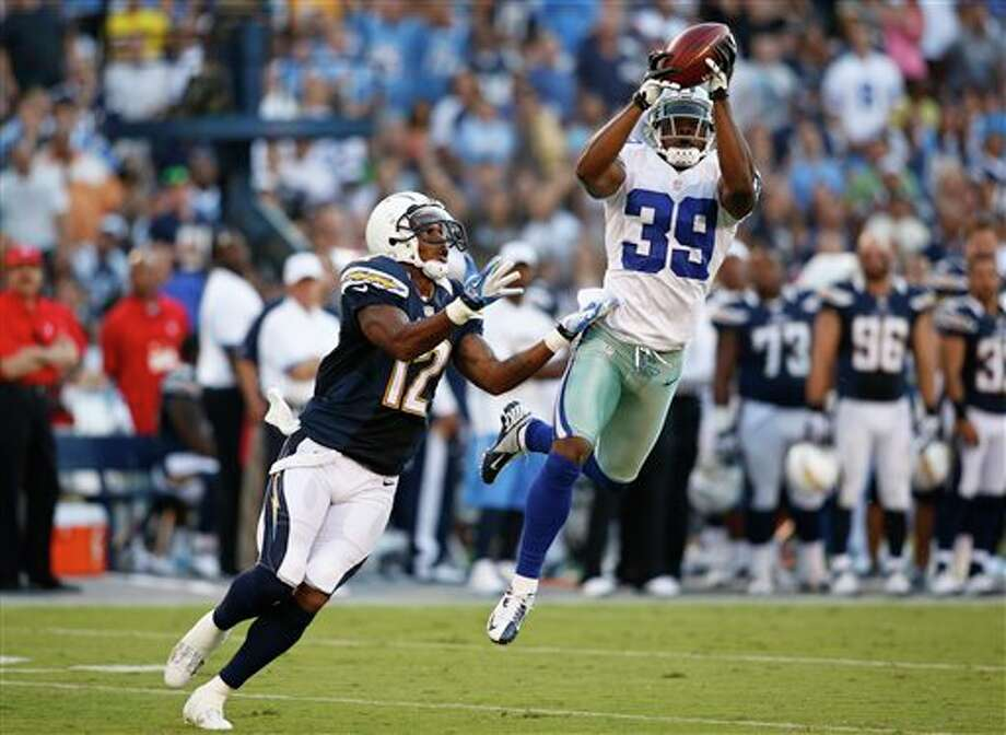 Dallas Cowboys defensive back Brandon Carr picks off a pass in front of San Diego Chargers wide receiver Robert Meachem during the first half  of a NFL preseason football game Saturday, Aug. 18, 2012 in San Diego. (AP Photo/Chris Park) Photo: Associated Press
