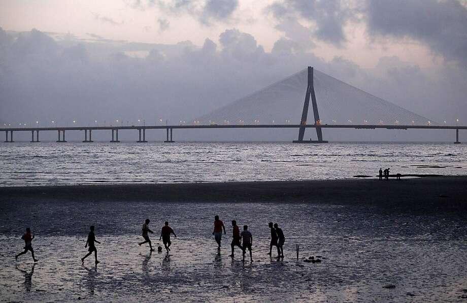 With the Bandra–Worli Sea Link in the background, men play football on the sea shore in Mumbai, India, Saturday, Aug. 18, 2012. Photo: Rajanish Kakade, Associated Press