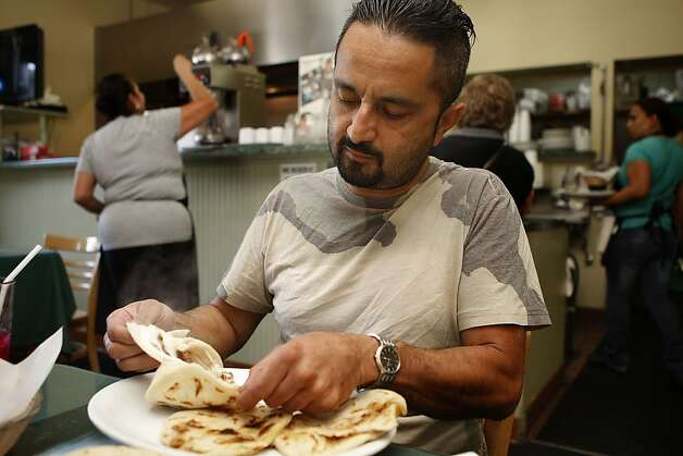 Nelson Duran (left) from Redwood City having pupusas at cafe and restaurant Montecristo in San Francisco , Calif., on Monday, August  13, 2012. Photo: Liz Hafalia, The Chronicle