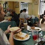 Francys Duran (right) from San Mateo taking a picture of her father Nelson Duran (left) from Redwood City holding pupusas at cafe and restaurant Montecristo in San Francisco.