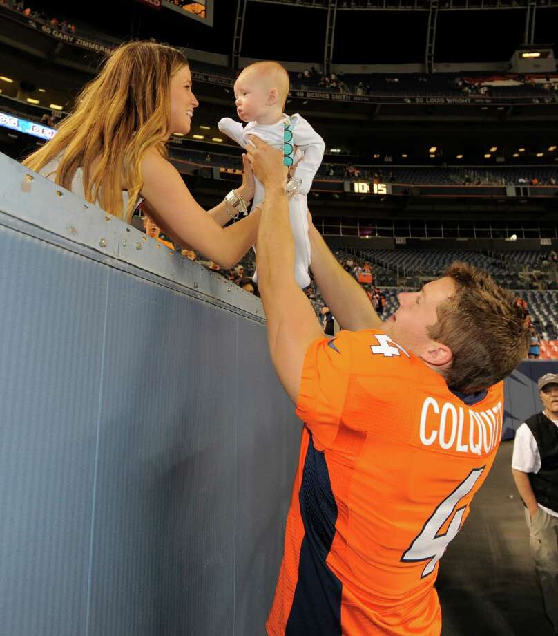 Denver Broncos' Britton Colquitt holds his son Nash as his wife Nikki looks on. Photo: AP