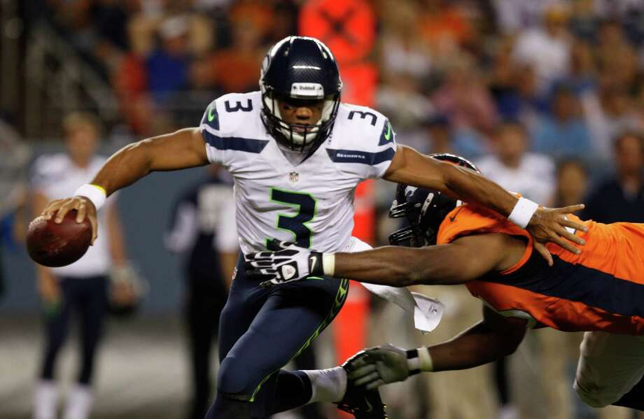 Denver Broncos defensive end Jeremy Beal, left, reaches out for Seattle Seahawks quarterback Russell Wilson in the second half. Photo: AP