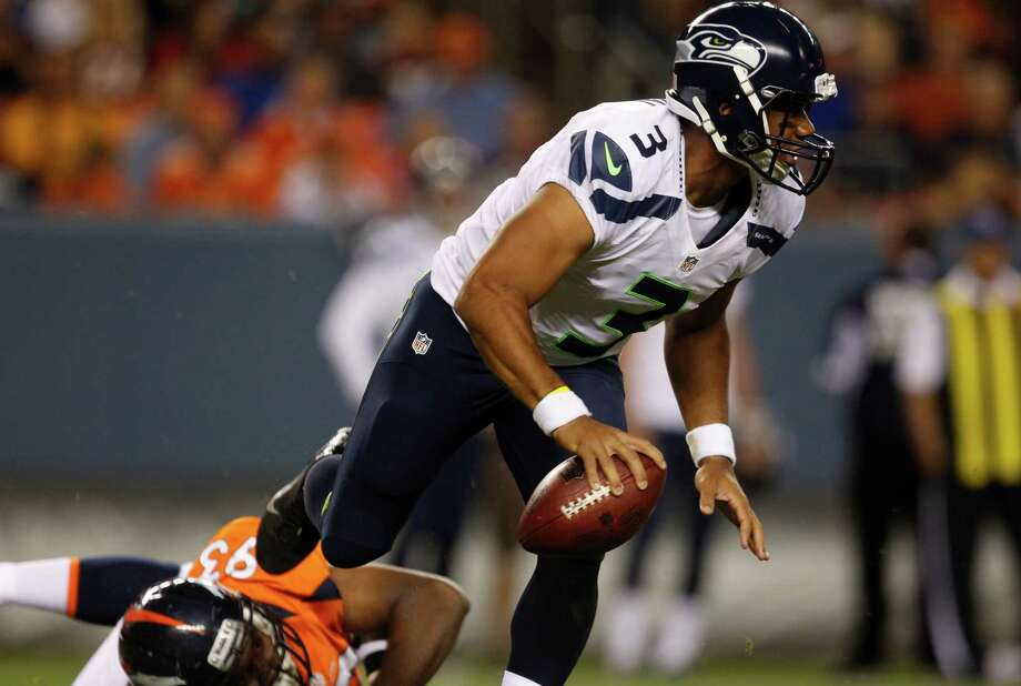 Seattle Seahawks quarterback Russell Wilson, front, evades a tackle by Denver Broncos defensive end Jeremy Beal in the second half. Photo: AP