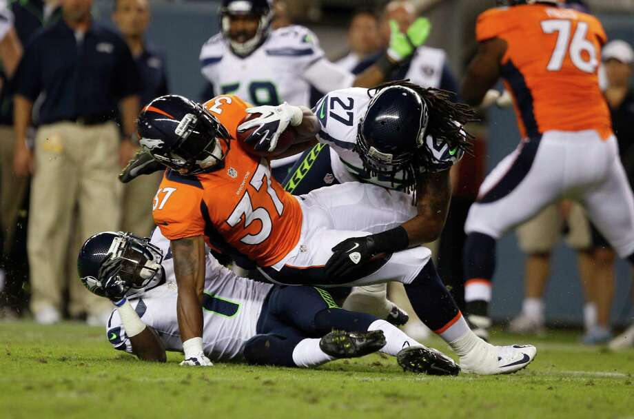 Denver Broncos runningback Jeremiah Johnson, front, is tackled by Seattle Seahawks strong safety Winston Guy in the second half. Photo: AP