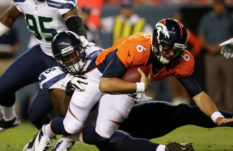 Denver Broncos quarterback Brock Osweiler, front, is sacked by Seattle Seahawks defensive end Greg Scruggs in the second half. Photo: AP