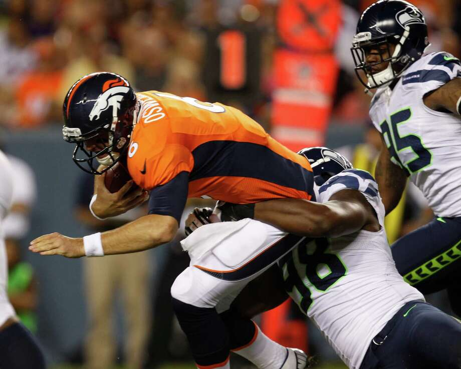 Denver Broncos quarterback Brock Osweiler, left, is sacked by Seattle Seahawks defensive end Greg Scruggs in the second half. Photo: AP
