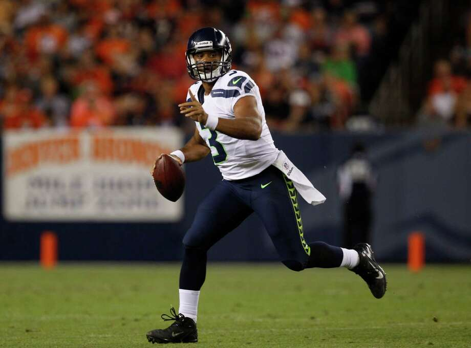 Seattle Seahawks quarterback Russell Wilson rolls out against the Denver Broncos in the second half. Photo: AP