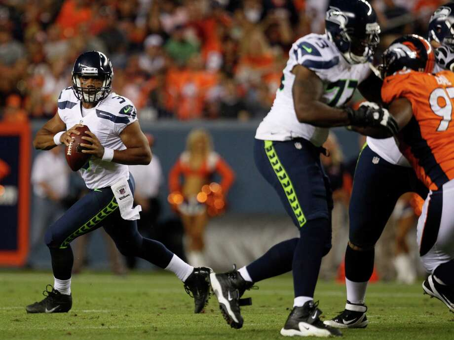 Seattle Seahawks quarterback Russell Wilson rolls out for a pass against the Denver Broncos in the second half. Photo: AP