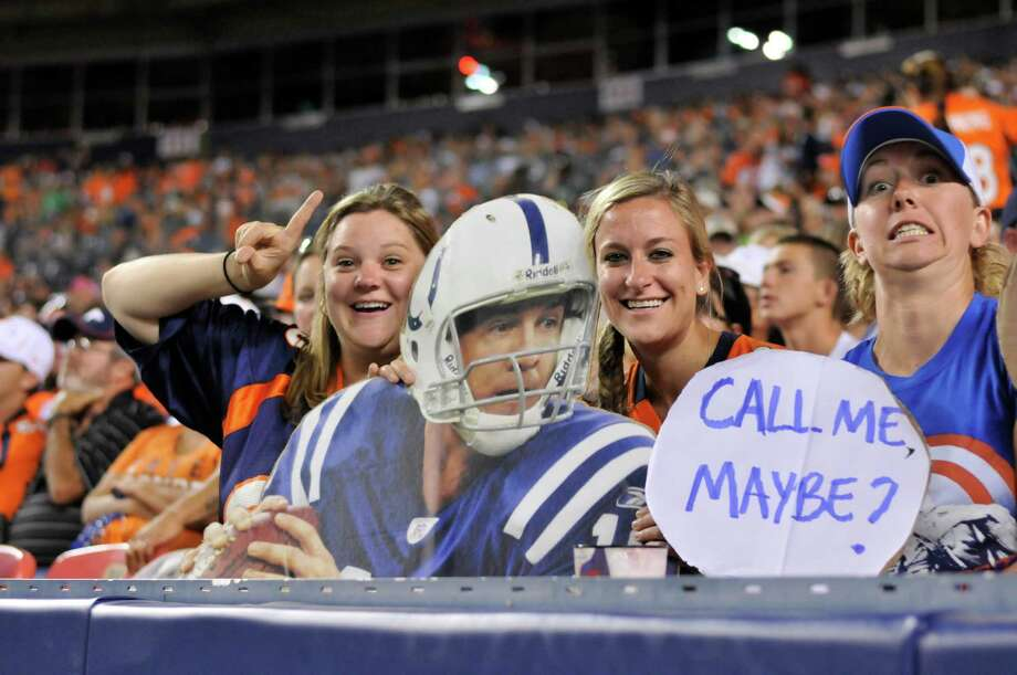 Fans pose with a cardboard cutout of Denver Broncos quarterback Peyton Manning in his old Indianapolis Colts uniform. Photo: AP