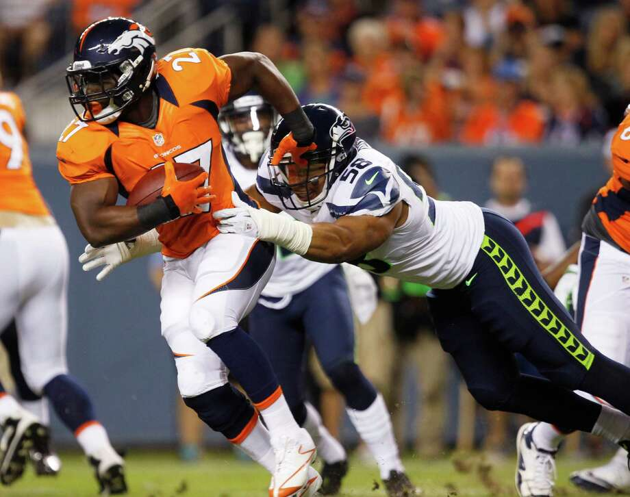 Denver Broncos'  Knowshon Moreno, left, carries the ball as Seattle Seahawks' Dexter Davis makes the tackle, in the second half. Photo: AP