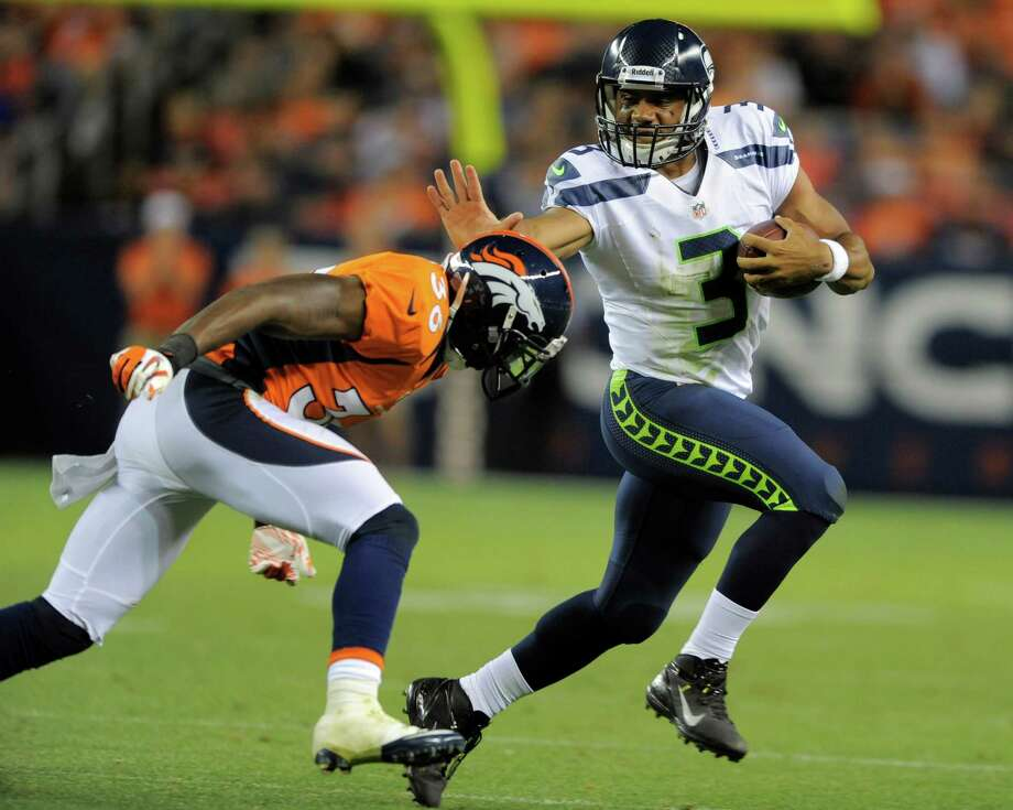 Seattle Seahawks quarterback Russell Wilson (3) stiff arms Denver Broncos defensive back Rafael Bush (36) in the second half. Photo: AP