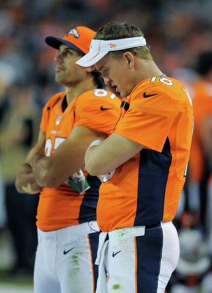 Denver Broncos quarterback Peyton Manning, right, stands on the sidelines late in the second half. T