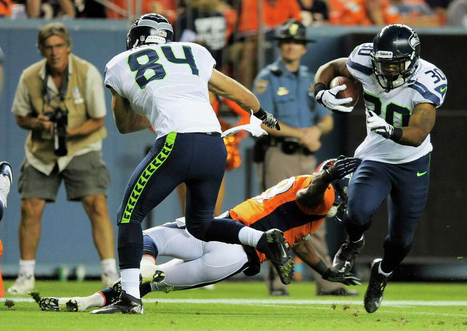 Seattle Seahawks' Tyrell Sutton, right, runs for a touchdown as Denver Broncos' Duke Ihenacho center, attempts the tackle and Seahawks' Cooper Helfet (84) looks on, in the second half. The Seahawks beat the Broncos, 30-10. Photo: AP