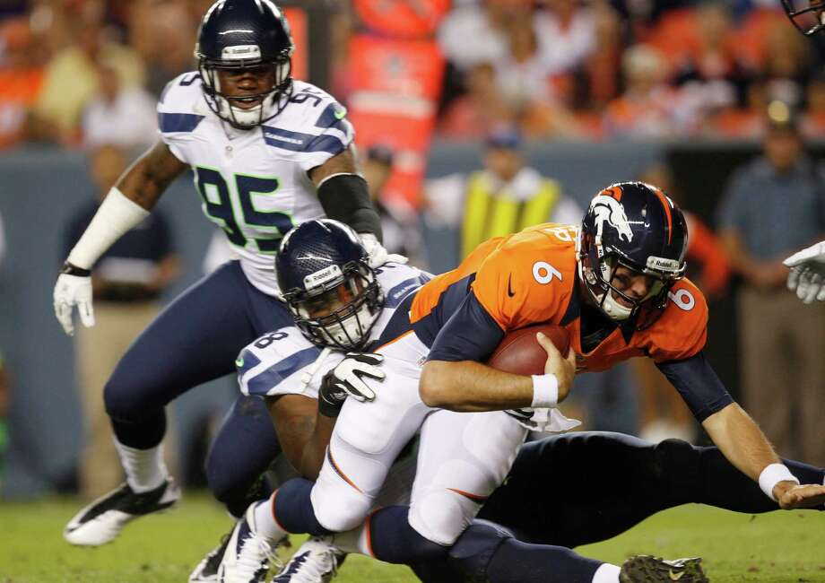 Denver Broncos quarterback Brock Osweiler (6) is sacked by Seattle Seahawks' Greg Scruggs as Seahawks' Pierre Allen (95) looks on, in the second half. Photo: AP