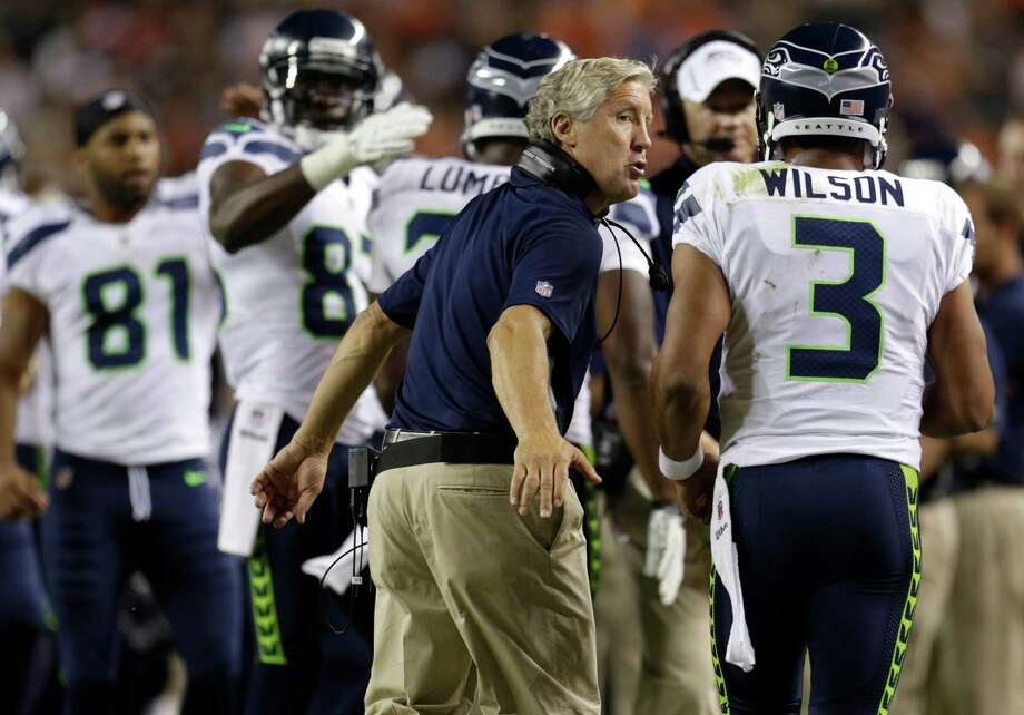 Seattle Seahawks head coach Pete Carroll greets quarterback  Russell Wilson (3) after a touchdown against the Denver Broncos in the second half. Photo: AP