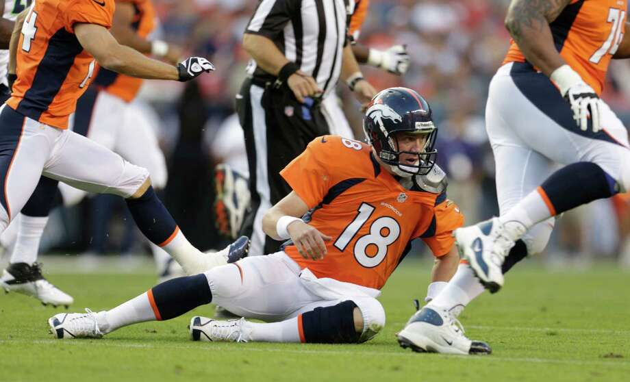 Denver Broncos quarterback Peyton Manning sits on the turf after throwing an interception against the Seattle Seahawks, in the first half. Photo: AP