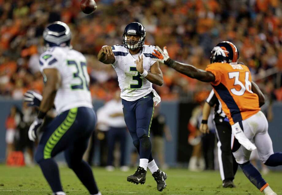 Seattle Seahawks quarterback Russell Wilson (3) makes a touchdown pass to Tyrell Sutton, left, as Denver Broncos'  Rafael Bush watches during the second half. Photo: AP