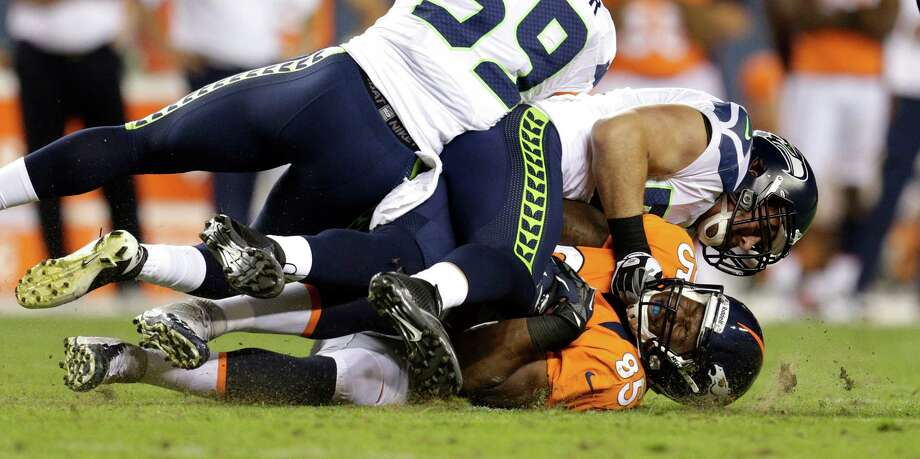Denver Broncos'  Virgil Green, bottom, is hit hard by Seattle Seahawks'  Barrett Ruud, center,and Korey Toomer, top, after catching the ball in the second half. Photo: AP