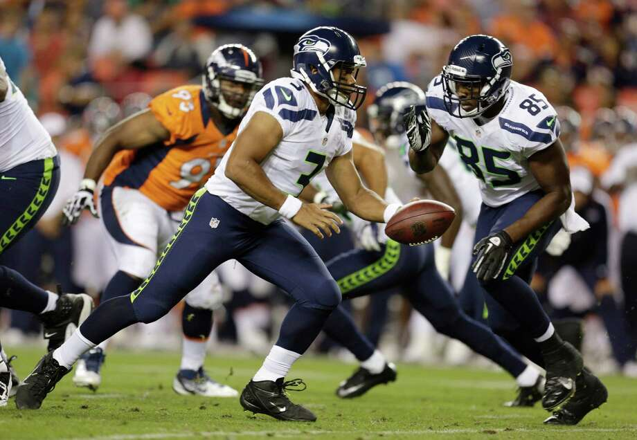 Seattle Seahawks quarterback Russell Wilson (3) hands off to Seahawks' Anthony McCoy (85) in the second half. Photo: AP