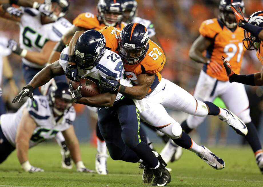 Denver Broncos' Wesley Woodyard (52) tackles Seattle Seahawks' Robert Turbin. Photo: AP