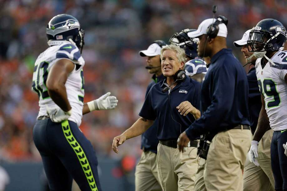 Seattle Seahawks head coach Pete Carroll, center, greets Sehawks' K.J. Wright, left, after Wright made an interception in the first half. Photo: AP
