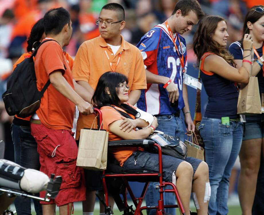Victims of the movie theater shooting in Aurora, Colo., join others on the field as they are recognized prior to the game. Photo: AP
