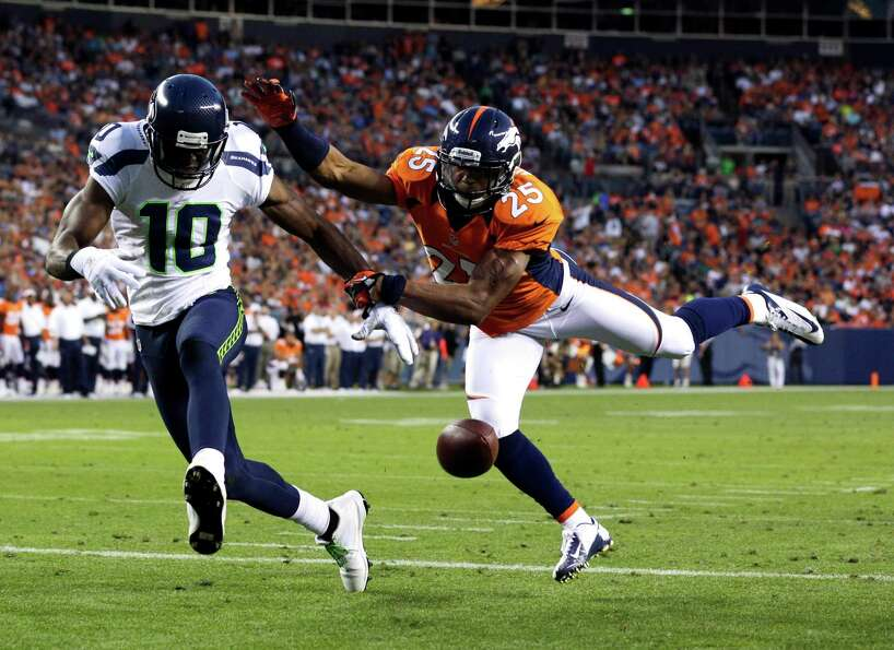 Denver Broncos' Chris Harris (25) breaks up a pass intended for Seattle Seahawks' Terrell Owens (10)