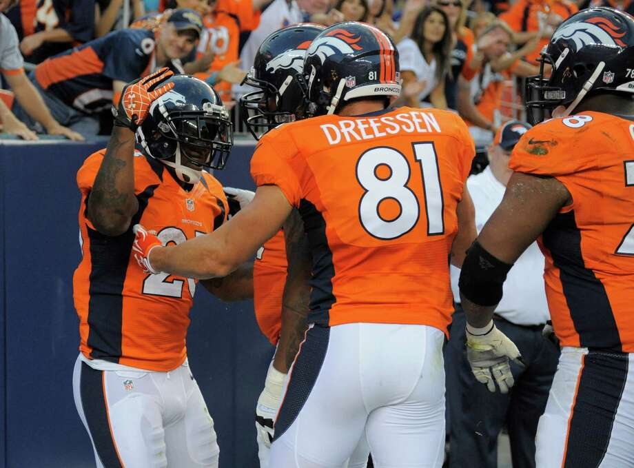 Denver Broncos' Willis McGahee, left, celebrates with Broncos' Joel Dreessen and other players after McGahee scored a touchdown against the Seattle Seahawks, in the first half. Photo: AP