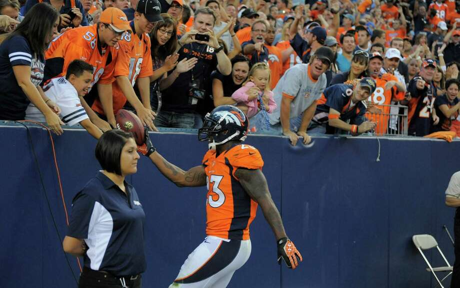 Denver Broncos' Willis McGahee gives the ball to a fan after he scored a touchdown against the Seattle Seahawks, in the first half. Photo: AP