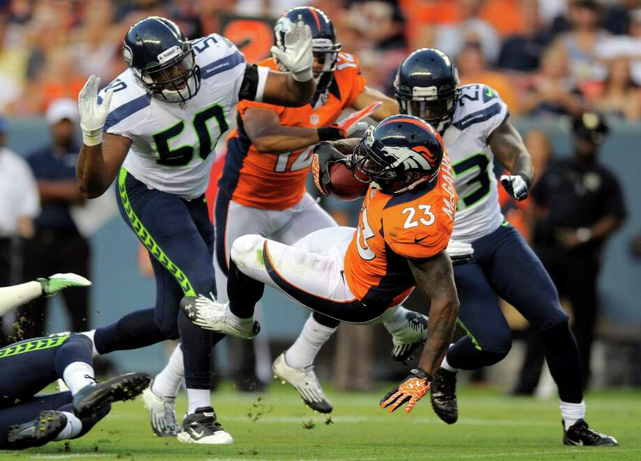 Denver Broncos'  Willis McGahee (23) carries the ball as Seattle Seahawks'  K.J. Wright (50) closes in during the first half. Photo: AP