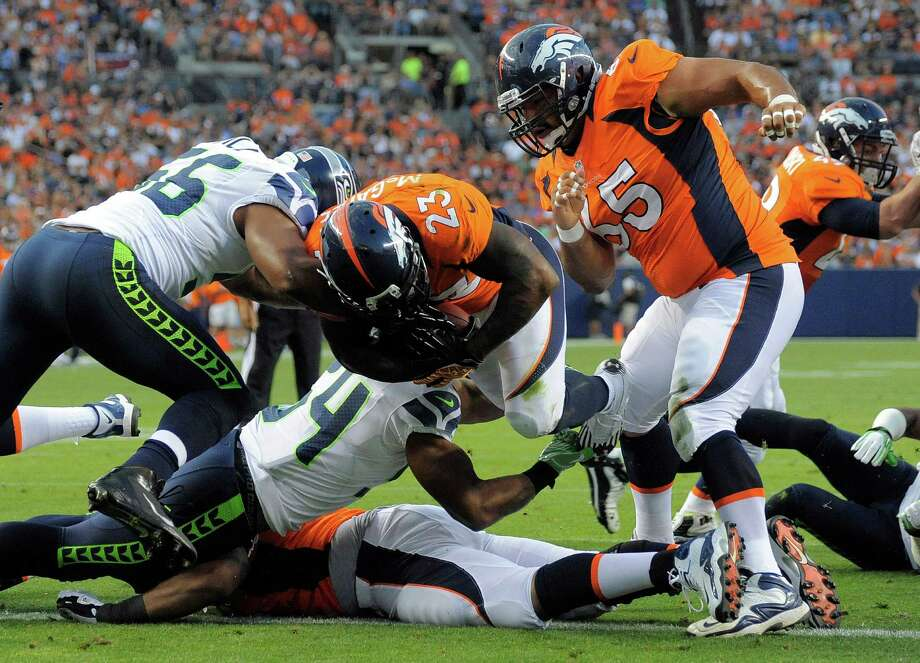 Denver Broncos' Willis McGahee (23) punches past the defense of Seattle Seahawks' Leroy Hill, left, to score a touchdown as Broncos' Manny Ramirez, right, looks on. Photo: AP
