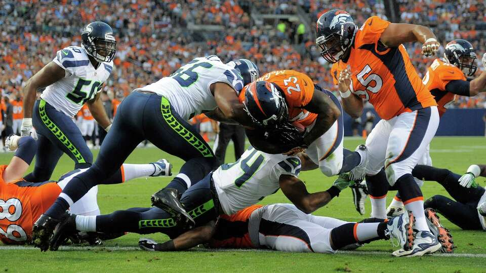 Denver Broncos' Willis McGahee (23) punches past the defense of Seattle Seahawks'  Leroy Hill, cente