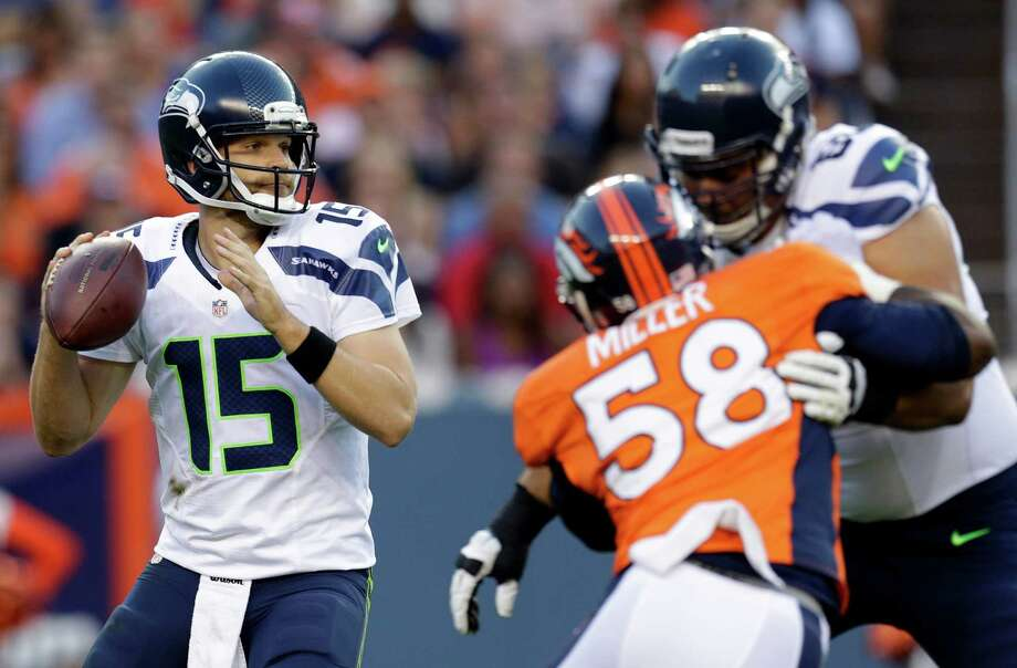 Seattle Seahawks quarterback Matt Flynn (15) looks to pass as Denver Broncos' Von Miller (58) blocks Seahawks'  Breno Giacomini, right,. Photo: AP