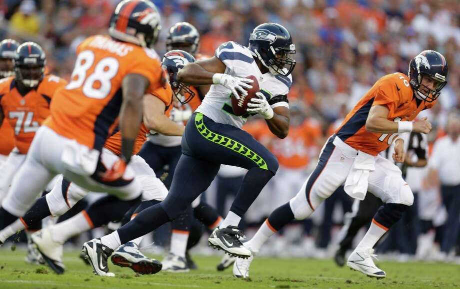 Denver Broncos quarterback Peyton Manning right, looks on as Seattle Seahawks'  K.J. Wright, center, runs with the ball he intercepted from Manning, in the first half. Photo: AP