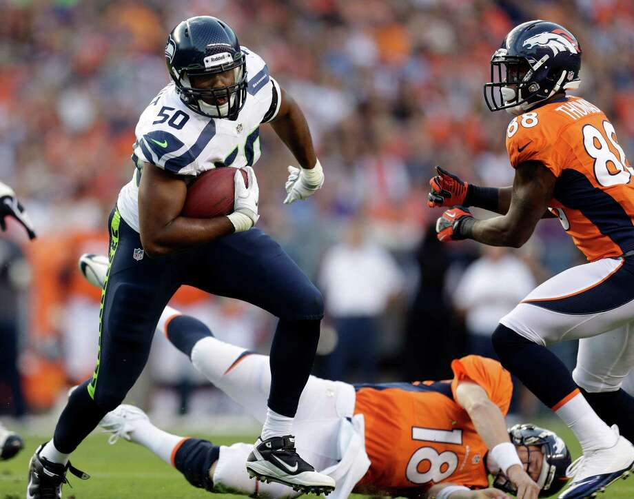 Denver Broncos quarterback Peyton Manning (18) lies on the turf as Seattle Seahawks' K.J. Wright (50) runs after intercepting a pass from him. Photo: AP
